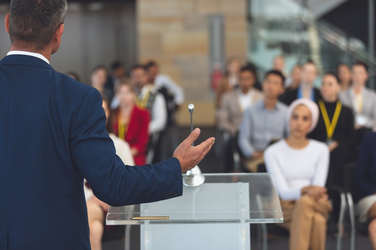 rear-view-of-mixed-race-businessman-speaking-at-a-LHFWVCR